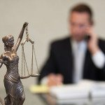 picture of lady justice statue in front of attorney John Tucker on the phone