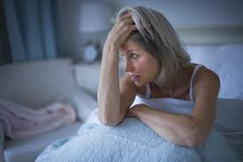 picture of woman sitting up in bed with head in hand because she cannot sleep