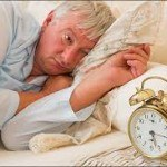 picture of man in bed looking at alarm clock showing 5:15 a.m.